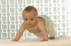 Baby boy (6-11 months) crawling Stock Photos
