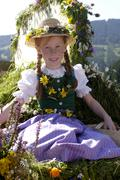 Austria, Salzburg land, Girl in traditional costume sitting in wagon Stock Photos
