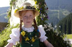 Austria, Salzburg land, Girl in traditional costume sitting in wagon - stock photo