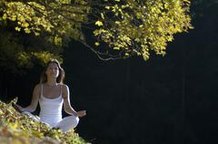 Young woman mediating in forest - stock photo