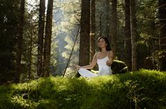 Young woman mediating in forest, looking away - stock photo