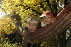 Stock Photo of Two boys (6-9) lying in hammock, portrait