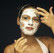 Stock Photo of Young woman applying face pack, close-up