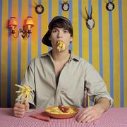 Young man eating French fries - stock photo