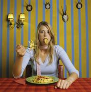 Young woman eating french fries - stock photo