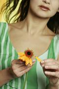 Woman plucking petals from flower, close up - stock photo