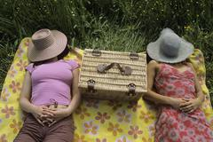Women relaxing in meadow with hat over face Stock Photos