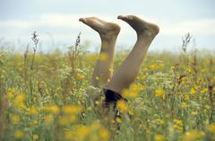 Woman with feet up in meadow, low section Stock Photos