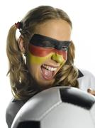 Stock Photo of Woman with German flag painted on face holding ball, close-up
