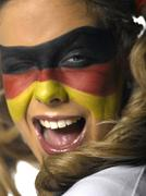 Woman with German flag painted on face winking, close-up - stock photo