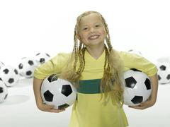 Stock Photo of Girl (8-11) holding soccer ball under arms, portrait