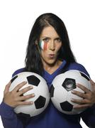 Woman with Italian Flag painted on her face,  holding footballs pouting Stock Photos