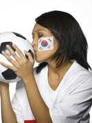 Stock Photo of Woman with Corean Flag painted on her face, kissing soccer ball, close-up