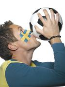 Young man with Sweden flag painted on face Stock Photos