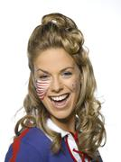 Young woman with American flag painted on face smiling, portrait - stock photo