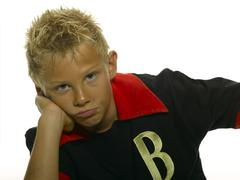 Boy in sportsdress looking bored Stock Photos