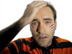 Man with Holland flag painted on face, portrait - stock photo