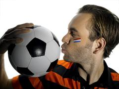 Stock Photo of Man with Holland flag painted on face, kissing soccer ball