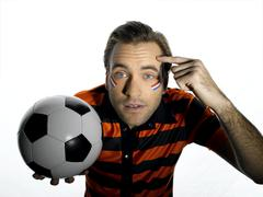 Man with Holland flag painted on face holding soccer ball, finger pointing on - stock photo