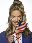 Young woman holding US flag, portrait - stock photo