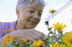 Stock Photo of Senior woman gardening, low angle view