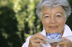 Senior woman holding cup of tea, close-up - stock photo