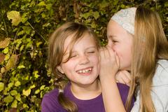 Girl (8-11) whispering in friend's ear, smiling Stock Photos