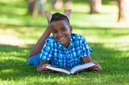 Stock Photo of outdoor portrait of student black boy reading a book - african people