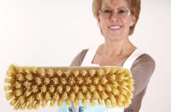 Mature woman holding broom - stock photo