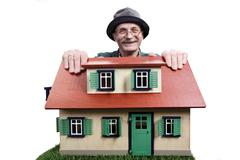 Old man with house, proud home owner - stock photo