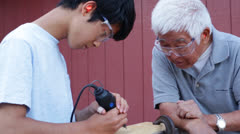 Stock Video Footage of Asian Senior Man with Grandson Using Carving Tool