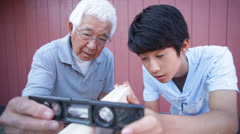 Stock Video Footage of Asian Senior Teaching Grandson How to Use a Level Tool