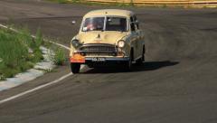 Vintage Morris Oxford one light broken moving slowly followed by Jaguar MkII - stock footage