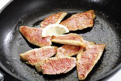 Filets of sea barb in pan, close-up - stock photo