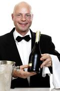 bartender holding bottle of sparkling wine, portrait - stock photo