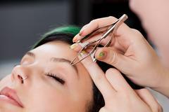 Hairdresser's hands using tweezers on woman's eyebrow Stock Photos