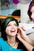 salon worker applying kajal on woman's eye - stock photo
