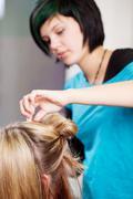 hairdresser making client's hair in salon - stock photo