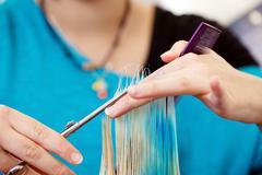 Female hairdresser cutting hair tips Stock Photos