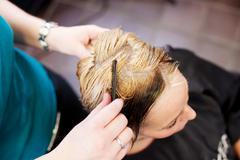 hair dresser combing client's hair in salon - stock photo