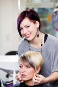 Female hairdresser checking hair length of customer in salon Stock Photos