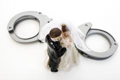 Wedding couple figurines and handcuff Stock Photos