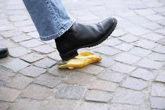 Human foot stepping on banana peel Stock Photos