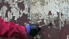 Scrapping old cracked paint from  old wooden  barn door Stock Footage