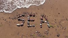 Word sea written on beach sand with wet stone Stock Footage