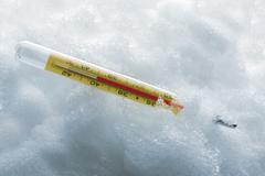 Clinical Thermometer in snow, close-up Stock Photos