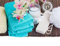 spa setting with towels, aroma candle and bath accessories - stock photo