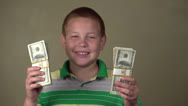 Stock Video Footage of Young boy with stacks of money smiling
