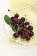 Sour cherries on glass plate, elevated view Stock Photos
