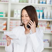 Pharmacist holding prescription paper while using cordless phone Stock Photos